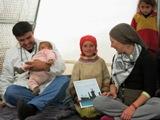 A questa bambina � stato necessario rasargli i capelli a zero perch� aveva i pidocchi. I volontari la consolano con un regalo. (Campo di Bab Al Salam, Siria - linea di confine)